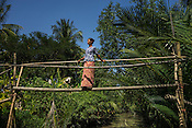 XXX poses for a photograph on a bridge over the creek in her village Hteik Chung next to Bogale river in Pyapon district of Myanmar. The village is next to the river where the tide comes in every 6 hours, rising the water levels considerably.