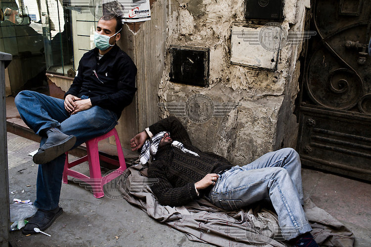 Protestors rest on a side street behind Tahrir Square. 25 January 2011 saw the beginning of a nationwide 18 day protest movement that eventually ended the 30-year rule of Hosni Mubarak and his National Democratic Party.