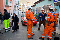 Isola del Giglio, Italy, January 19, 2012. A nun walks by employees of a wreck removal and salvage operations company befire they work on the cruise liner Costa Concordia aground in front of the harbour of the Isola del Giglio (Giglio island) after hitting underwater rocks.