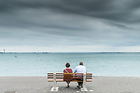 A couple relax on a bench overlooking the Thames Estuary at Southend in essex.