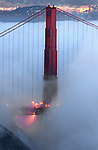 The fog slowly rolls past the Golden Gate Bridge as it steams down the Marin headlands in San Francisco, California.