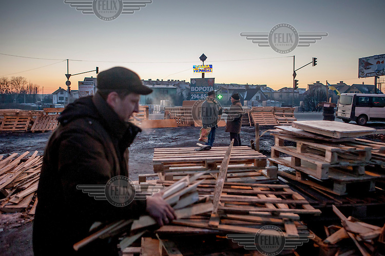 Oleg, an anti-government activist, gathers wood for a fire at a barricade at the Epicenter building supplies store. Protests against the government of President Viktor Yanukovych were sparked on 21 November 2013 by the Ukrainian government's decision to suspend preparations for the signing of an association agreement with the European Union that would have increased trade with the EU. Some believe that the U-turn came about as a result of pressure from President Putin of Russia who wants Ukraine to join a customs union with itself, Kazakhstan and Belarus. Russia offered 15 billion dollars of soft loans and reduced price gas to Ukraine at the same time as discussions with the EU were taking place.