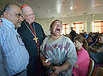 Cardinal Timothy Dolan, the archbishop of New York, listens to Amal Mare during a visit to a camp for internally displaced families in Ankawa, near Erbil, Iraq, on April 9, 2016. Dolan, chair of the Catholic Near East Welfare Association, is in Iraqi Kurdistan with other church leaders to visit with Christians and others displaced by ISIS. Mare began sobbing while asking Dolan how long it would be until she and her family could return to their home in Qaraqosh. She said they had been praying the rosary every night, but were tired of living in misery and wanted to go home.<br /> <br /> On the left is Michel Constantin, the CNEWA emergency response coordinator for the region.