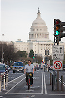 A bicycle commuter rides in the bicycle lane on Pennsylvania avenue with the Capitol dome in the background in Washington DC