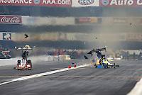 Feb 9, 2014; Pomona, CA, USA; NHRA top fuel dragster driver Sidnei Frigo (right) blows a tire after he explodes an engine alongside Doug Kalitta during the Winternationals at Auto Club Raceway at Pomona. Mandatory Credit: Mark J. Rebilas-