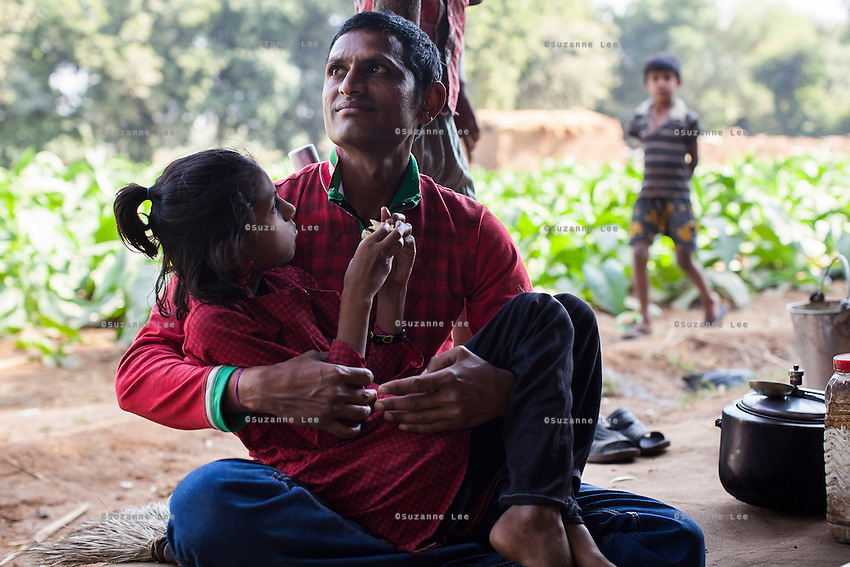 Dhiraj Khristi, 36, hugs his daughter at their farm house in Anand, Gujarat, India on 9th December 2012. While Dhiraj and his wife Pinki used to make 2000-5000 rupees per month from farming and as labourers, she had made over 850,000 from both her surrogacies and had bought land, buffaloes and saved 320,000 rupees in a fixed deposit that they plan to use for their daughter's future education. Photo by Suzanne Lee / Marie-Claire France