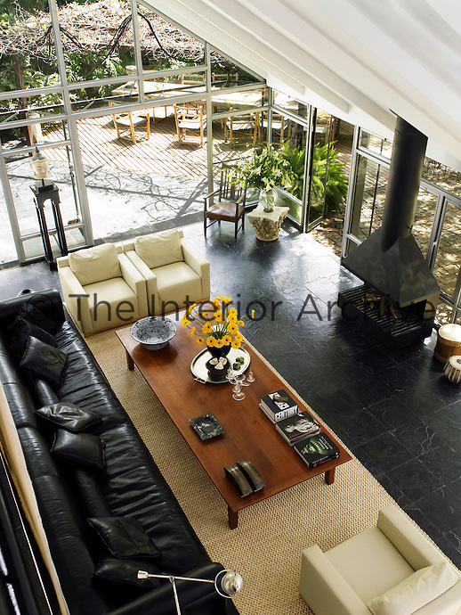 A overhead view of a spacious living room in a glass conservatory with a wood burning stove. Three boxy armchairs designed by Alex Meitlis are covered in a vinyl known in Israel as Prada plastic; a 14-foot leather sofa imported from Italy. The black fireplace designed by Joshua Kastiel  dominates the space and contributes to the black-and-white palette.
