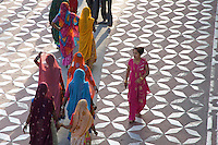 Visiting the The Taj Mahal in Agra,India Women from Jodhpur in Rajasthan in their traditional colorful dress craeting a spectacle in design and color in contarst to the white Marble of the Taj