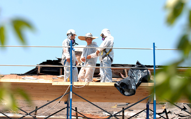 A worker wears a make-shift sombrero to protect from the 90 degree heat, Thursday, on the roof of Eastern Market.