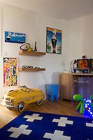 A boy's bedroom has a traditional blue colour scheme and a collection of impressive toys