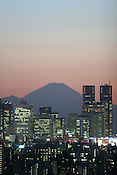 Mount Fuji standing behind the Nishi-Shinjuku skyscraper district, at dusk, in Tokyo, Japan, on Wednesday, Feb. 28, 2007.