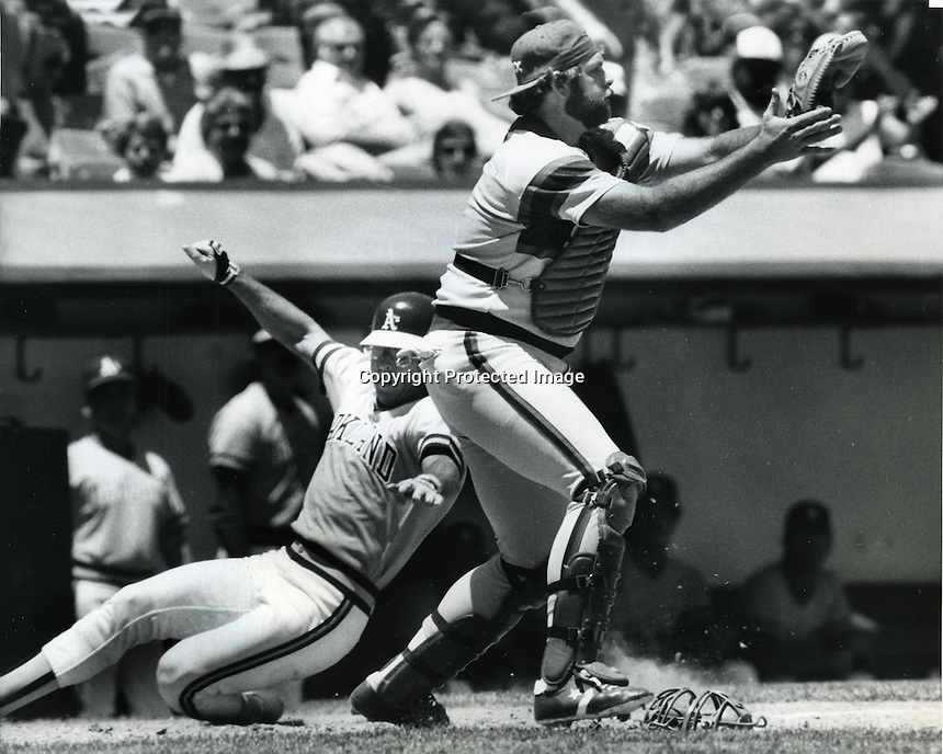 Oakland A's Bruce Bochte slides safely into home, White Sox catcher Marc Hill. (1985 photo by Ron Riesterer/Photoshelter)