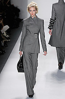 Model walks runway in a black+ivory loro piana cashmere/wool herringbong assymetric upturened peak lapel trouser suit w/mother of pearl imperial frame brooch, from the Zang Toi Fall 2012 &quot;Glamour At Gstaad&quot; collection, during Mercedes-Benz Fashion Week New York Fall 2012 at Lincoln Center.