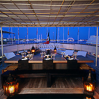 A large dining table under the canopy on Alberti Ferretti's houseboat laid out for dinner and lit with candles