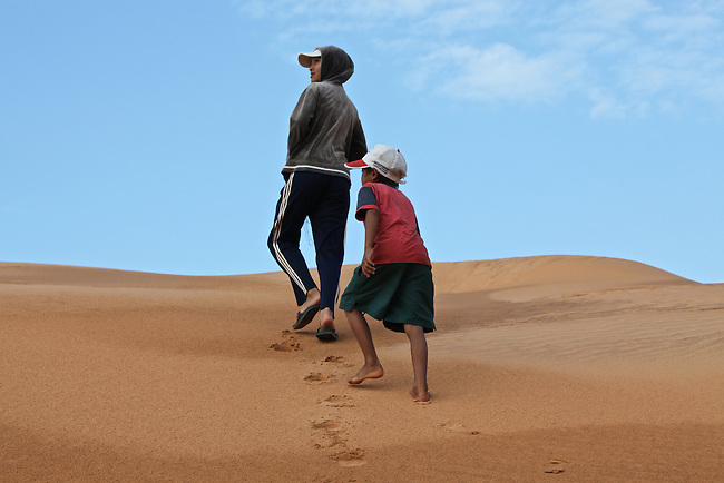 A girl and a boy walk up a hill at the red dunes near Mui Ne, Vietnam. Nov. 11, 2011.