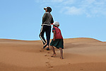 A girl and a boy walk up a hill at the red dunes near Mui Ne, Vietnam. Nov. 11, 2011.