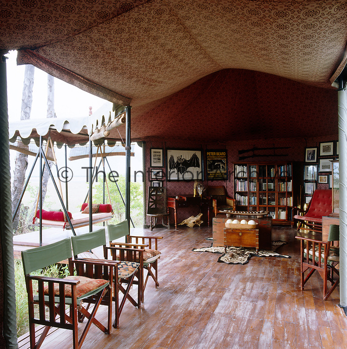 The swing bed which hangs beyond the library tent is the most hotly contested seat in the camp