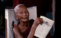 A OLD BUDDHIST MONK READING HIS SCRIPTURE IN A MONASTERY IN YANGON, MYANMAR, BURMA
