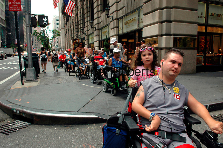Piper L. Wallenstein, age 6 rides on the back of her dad, Craig J. Wallenstein's wheelchair as they roll up Fifth Avenue on July 30, 2006 during the march and rally to celebrate the 16th anniversary of the Americans with Disabilities Act, sponsored by Disabled in Action of Metropolitan New York.  Disabled people and their  families and  supporters marched up Fifth Avenue from Rockefeller Center to Columbus Circle for the rally.  (© Frances M. Roberts)