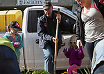 Athens Mayor Steve Patterson digs up weeds and plants flowers in front of the City Building with his family and fellow volunteer Emily Addams, right, during Athens Beautification Day on April 9, 2017.
