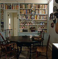 Decorative bowls add colour to this wall of book shelves built around the doorway of the dining room