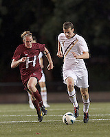 Boston College defender Nick Butler (4) brings the ball forward as Harvard University defender Philip Fleischman (16) closes.Boston College (white) defeated Harvard University (crimson), 3-2, at Newton Campus Field, on October 22, 2013.