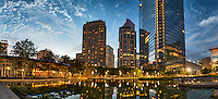 This is the Discovery Green in Houston after dark with the high rise building in the city with their lights on and the reflections in the lake of the city skyline. Watermark will not appear on image