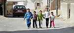 Syrian refugee children walk along a street in Amman, Jordan.