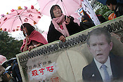 American President, George W. Bush, appears on a replica Japanese Yen banknote during a Peace demonstration, and Anti-War demonstration, in the rain, Hibiya Park, Tokyo on the one year anniversary of the USA led war on Iraq.