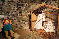 "Switzerland. Canton Tessin. Vira Gambarogno. The old town shows an exhibit of various Nativity scenes, illuminated at night for the Christmas holiday season. A Nativity Scene, may be used to describe any depiction of the Nativity of Jesus in art, but in the sense covered here, also called a crib or in North America and France a crèche (meaning ""crib"" or ""manger"" in French). It means a three-dimensional folk art depiction of the birth or birthplace of Jesus, either sculpted or using two-dimensional (cut-out) figures arranged in a three-dimensional setting. Christian nativity scenes, in two dimensions (drawings, paintings, icons, etc.) or three (sculpture or other three-dimensional crafts), usually show Jesus in a manger, Joseph and Mary in a barn (or cave). Stone walland a puppet.  © 2007 Didier Ruef"