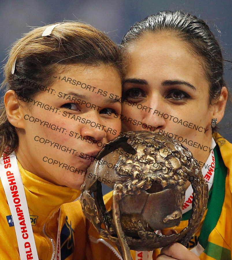 BELGRADE, SERBIA - DECEMBER 22:  Goalkeeper Mayssa Pessoa (L) and Fabiana Diniz (R) of Brazil kiss the tournament trophy during award ceremony on the World Women's Handball Championship 2013 at Kombank Arena Hall on December 22, 2013 in Belgrade, Serbia. (Photo by Srdjan Stevanovic/Getty Images)