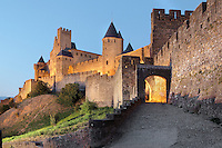 Aude Gate and Comtal Castle, with square Pinte Tower on the left, Justice Tower on the right, Citadel of Carcassonne, Aude, France. Carcassonne was a stronghold of Occitan Cathars during the Albigensian Crusades but was captured by Simon de Montfort in 1209. He added extra fortifications and Carcassonne became a citadel on the French border with Aragon. The fortress restored in 1853 by Eugene Viollet-le-Duc. Today it is a UNESCO World Heritage site. Picture by Manuel Cohen