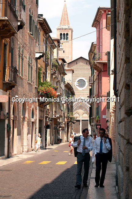 Two men in suites walk down a street in Verona, Italy with the Basilica di Santa Anastasia in the background.