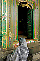 A woman prays at the entrance of a Mosque.