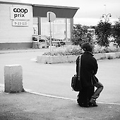 Man sitting on his suitcase wating for the bus in Vadsö North Norway