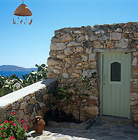 The entrance to this rustic stone cottage is through a small painted door