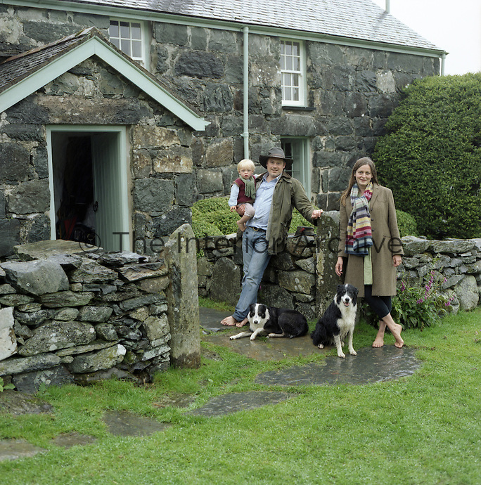 Portrait of architects Johnathan Holland and Jane Hackett  with their son and dogs outside their house