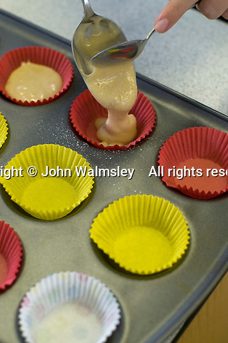 Gently putting just the right amount of cakemix into the cupcake cases, Food Technology class, state secondary School.