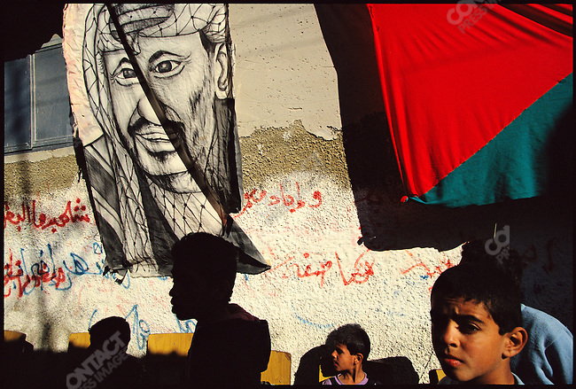 Yasser Arafat supporters mill about near a painting of the PLO chairman. Gaza City, Gaza. December 1993