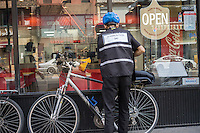 A deliveryman at a Domino's Pizza in New York prepares his bicycle outside of the store in the Chelsea neighborhood of New York on Sunday, May 29, 2016.  (© Richard B. Levine)