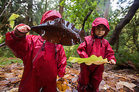 Fiddlehead students Audette Laird, and Amalie Brenner, right, both 3, play with Magnolia leaves on a hike in the Washington Park Arboretum during Fiddleheads Forest School, a nature preschool.