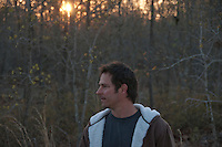 Man looking off  in the woods during a sunset