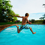 Boy jumping in swimming pool in South Africa.