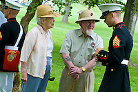 Senior citizens and young US Marine discuss experiences  Loyalty day patriotic parade in small town USA.