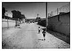 Children running along an alleyway lined with walls and barbed wire near the wall compound of a foreign NGO in Karta Parwan district of Kabul, Afghanistan.