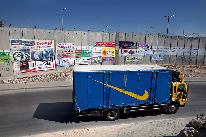 "June 2013, Ramallah, West Bank. On the road to the checkpoint leading to Jerusalem, with the Israeli separation wall closing the West Bank from Jerusalem. ""85% of the barrier's planned route runs through the West Bank.  By July 2012, construction of the barrier was 62% complete.  Construction of the barrier in the West Bank gravely violates the rights of Palestinians in the areas affected, restricting their access to their lands, crucial services and relatives on the other side of the barrier. The barrier also prevents any possibility of economic development. "" (B'Tselem, Human rights Israeli NGO)"