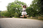 Jumping in the Park. Mid 20's brunette woman in white jumps high in the air out of joy over her success, victory, achievement.