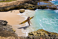 Young woman standing in ocean with surfboard at Makaha