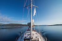 Deparding Tromsø by sailboat into blue skies and calm water, Norway