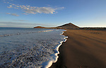 Movement in the waves. El Medano beach, with red mountain in background. Tenerife, Canary Islands.